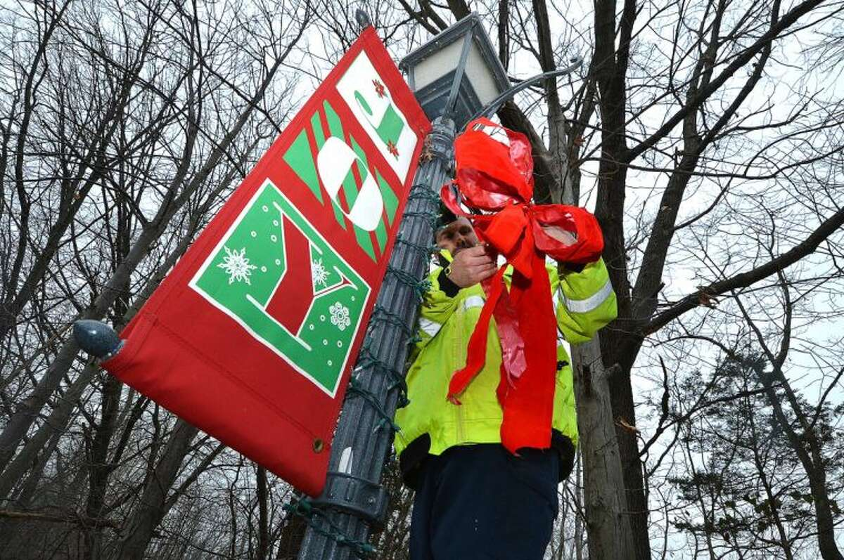 Hour Photo/Alex von Kleydorff Wilton Parks and Grounds Lead Man Bruno Mignogna places a red bow on a lamp post after setting the Joy banner and a string of lights on one of the 50 plus lamposts in Wilton Center on Monday, adding holiday color to the center.
