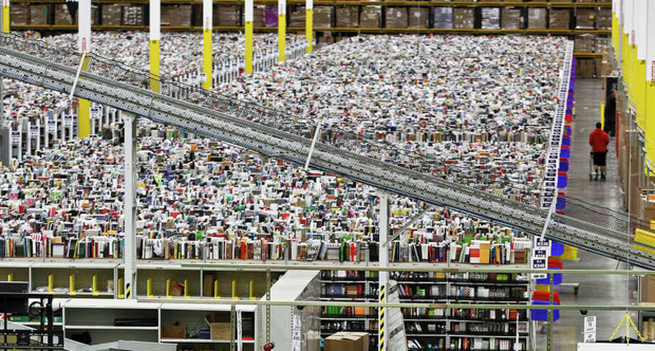 FILE - In this Monday, Nov. 26, 2012, file photo, an employee walks a wide isle at Amazon.com's 1.2 million square foot fulfillment center, in Phoenix. Millions of shoppers are expected to click on items on Monday, Dec. 2, 2013, as retailers rev up deals to grab online holiday shopping dollars on the first working day after the busy holiday weekend. (AP Photo/Ross D. Franklin, File) / AP