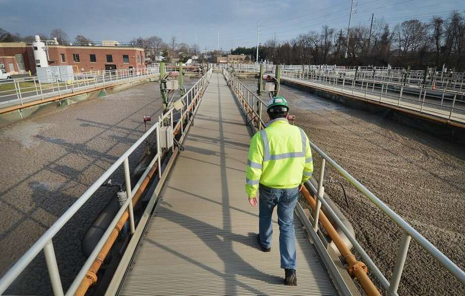 Hour Photo/Alex von Kleydorff . Norwalk Waste water Treatment Plant Chief Operator Bob Sardaro, with CH2M HILL,inc walks along the Secondary Treatment Aeration Tanks that help process up to the 14 million gallons of waste water a day