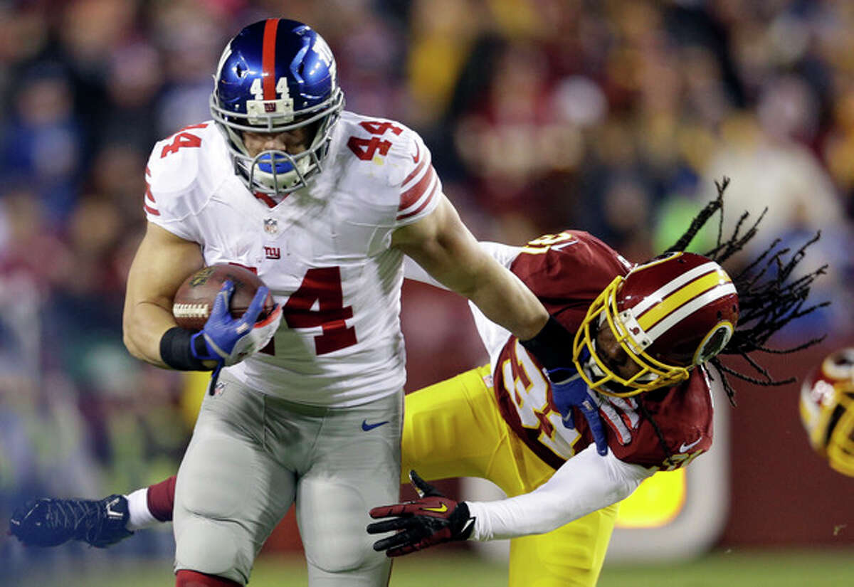 New York Giants running back Peyton Hillis (44) pushes away Washington Redskins strong safety Brandon Meriweather (31), for a first down, during the first half of an NFL football game Sunday, Dec. 1, 2013, in Landover, Md. (AP Photo/Patrick Semansky)