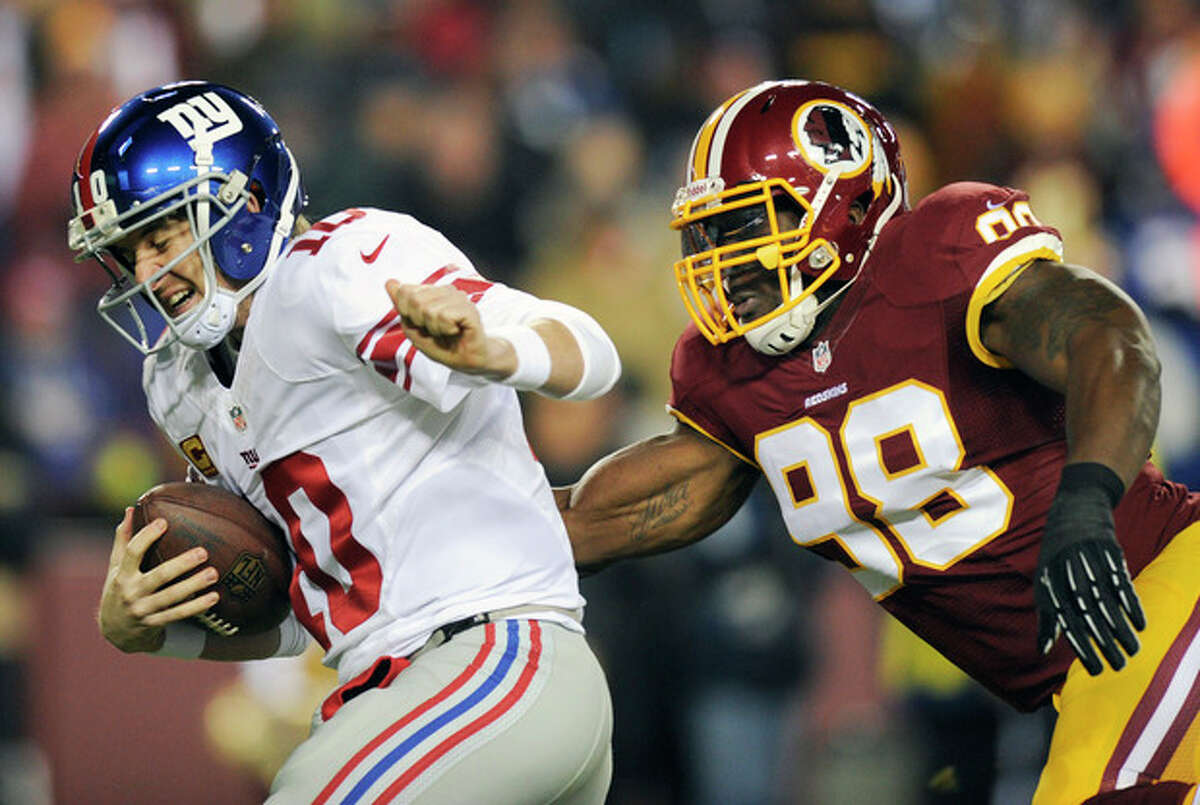New York Giants quarterback Eli Manning, left, is sacked by Washington Redskins outside linebacker Brian Orakpo (98) during the first half of an NFL football game Sunday, Dec. 1, 2013, in Landover, Md. (AP Photo/Nick Wass)