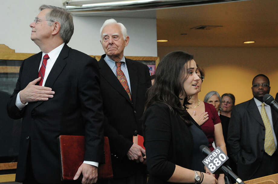 Stamford Mayor-elect David Martin listens as his daughter sings the national anthem Monday at his swearing in ceremony in the lobby of the Government building in Stamford. photo/Matthew Vinci