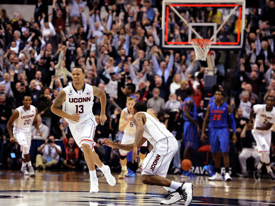 Connecticut's Shabazz Napier, left, and Ryan Boatright, right, react after Napier hits the game winning basket at the end an NCAA college basketball game against Florida, Monday, Dec. 2, 2013, in Storrs, Conn. Connecticut won 65-64. (AP Photo/Jessica Hill) / FR125654 AP