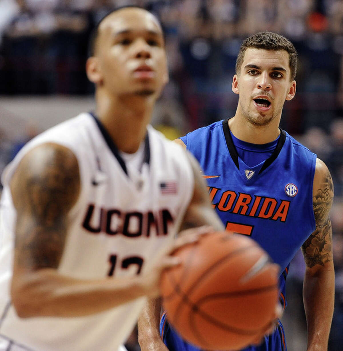 Florida's Scottie Wilbekin, right, watches Connecticut's Shabazz Napier shoot a free throw during the first half of an NCAA college basketball game, Monday, Dec. 2, 2013, in Storrs, Conn. (AP Photo/Jessica Hill)