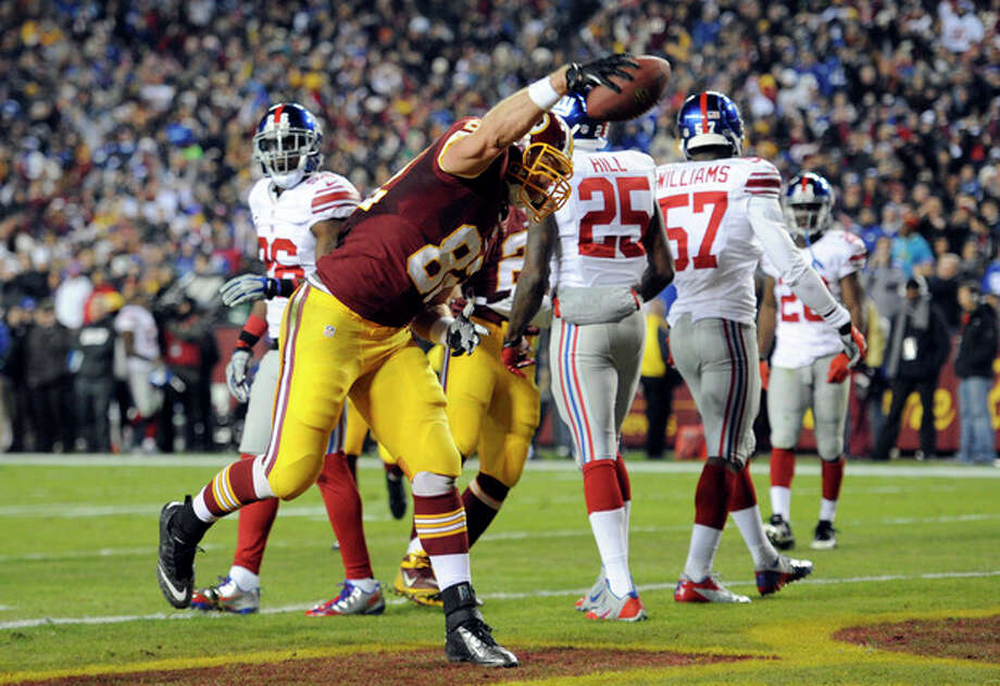 Washington Redskins tight end Logan Paulsen (82) spikes the football after his touchdown during the first half of an NFL football game against the New York Giants Sunday, Dec. 1, 2013, in Landover, Md. (AP Photo/Nick Wass) / FR67404 AP