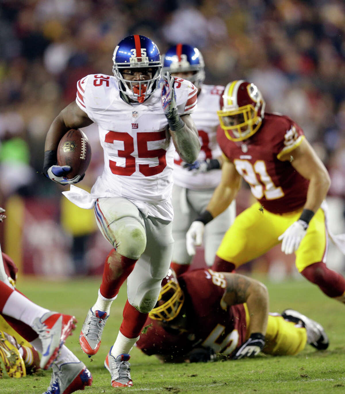 New York Giants running back Andre Brown (35) gets away from Washington Redskins nose tackle Chris Neild (95), to score a touchdown, during the first half of an NFL football game Sunday, Dec. 1, 2013, in Landover, Md. (AP Photo/Patrick Semansky)