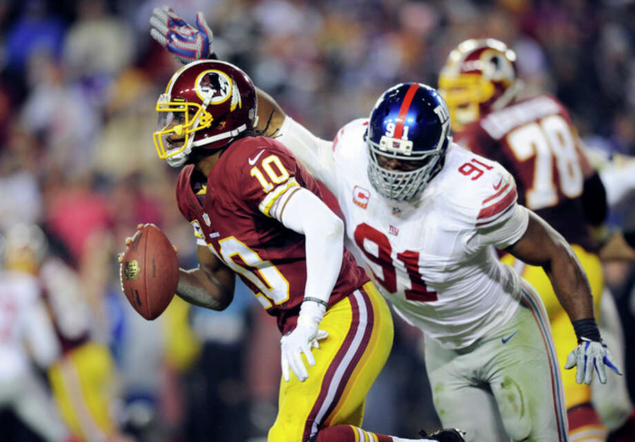 Washington Redskins quarterback Robert Griffin III (10) is pressured by New York Giants defensive end Justin Tuck (91) during the second half of an NFL football game Sunday, Dec. 1, 2013, in Landover, Md. The Giants won 24-17. (AP Photo/Nick Wass) / FR67404 AP