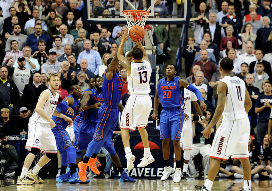 Connecticut's Shabazz Napier (13) goes up for the game winning basket at the buzzer during the second half of an NCAA college basketball game against Florida, Monday, Dec. 2, 2013, in Storrs, Conn. Connecticut won 65-64. (AP Photo/Jessica Hill) / FR125654 AP