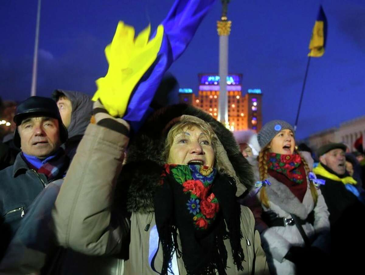 Protesters shout during a rally at the central Independence Square in Kiev, Ukraine, Monday, Dec. 2, 2013. Thousands of Ukrainian protesters on Monday besieged government buildings in Kiev and called for the ouster of the prime minister and his Cabinet, as anger at the president's decision to ditch a deal for closer ties with the European Union gripped other parts of the country and threatened his rule. (AP Photo/Sergei Grits)