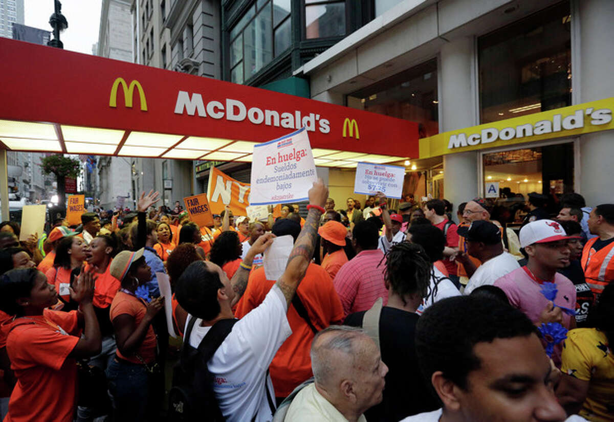 FILE - In this Thursday, Aug. 29, 2013, file photo, protesting fast food workers demonstrate outside a McDonald's restaurant on New York's Fifth Avenue, in New York. Fast-food workers in about 100 cities will walk off the job Thursday, Dec. 5, 2013, to build on a campaign that began about a year ago to call attention to the difficulties of living on the federal minimum wage of $7.25 an hour. (AP Photo/Richard Drew, File)