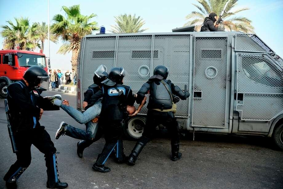 Egyptian riot police detain a protester as they disperse a demonstration in Alexandria, Egypt, Monday, Dec. 2, 2013. Black clad riot police fired tear and chased dozens of rights activists and protesters who held a demonstration in the Mediterranean city demanding abolishing a new law that extensively restricted the right to hold a protest, imposing fines and jail terms on violators.(AP Photo/Heba Khamis) / AP