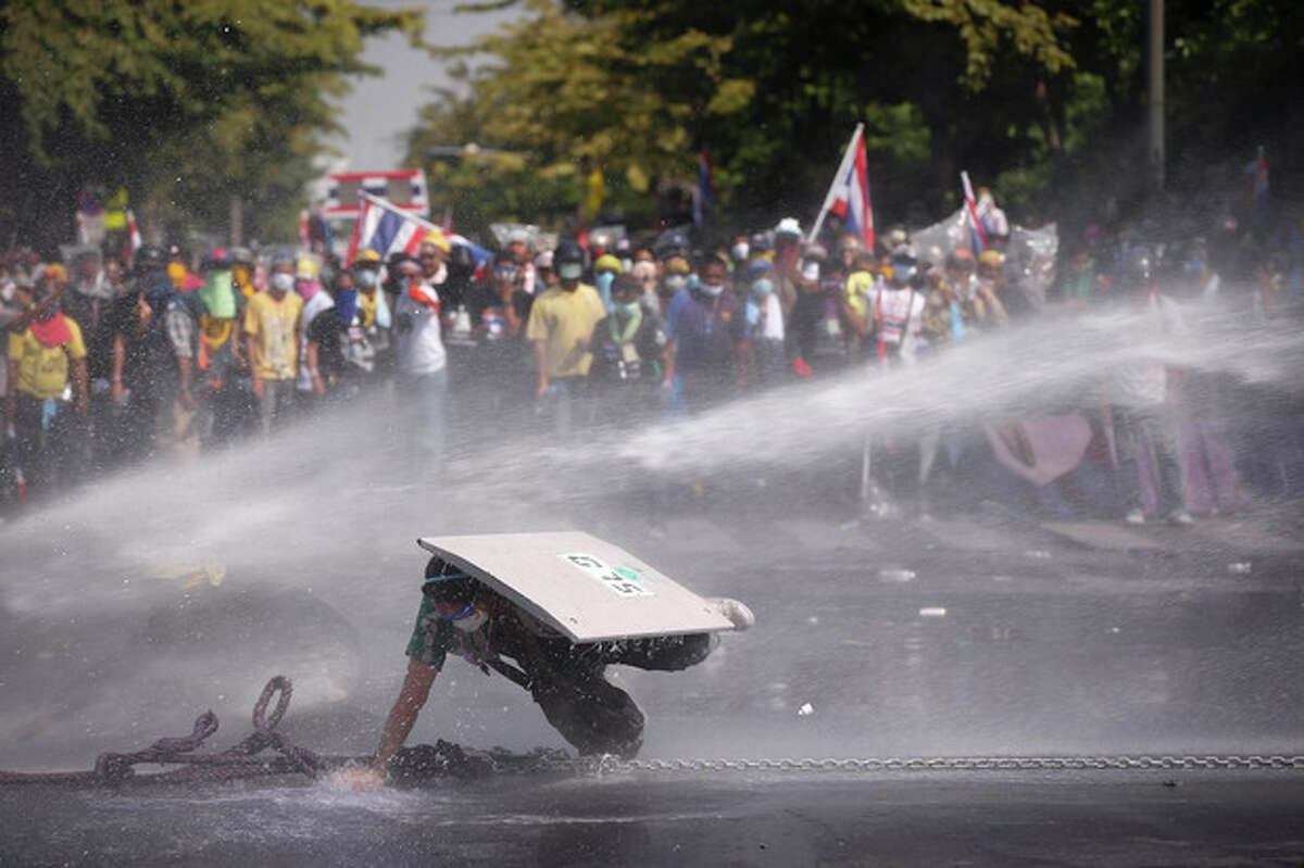 An Anti-government protester falls as he is hit by water cannon by police in Bangkok, Thailand, Monday, Dec 2, 2013. After a weekend of chaos in pockets of Bangkok, protesters vowed to push ahead with plans to topple Prime Minister Yingluck Shinawatra by occupying her office compound along with other key government buildings. Police again used tear gas on thousands of protesters on Monday after repeatedly driving them back with similar attacks throughout Sunday. (AP Photo/Vincent Thian)