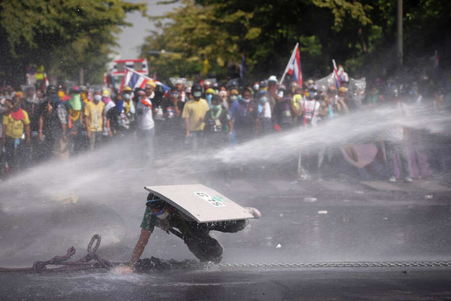 An Anti-government protester falls as he is hit by water cannon by police in Bangkok, Thailand, Monday, Dec 2, 2013. After a weekend of chaos in pockets of Bangkok, protesters vowed to push ahead with plans to topple Prime Minister Yingluck Shinawatra by occupying her office compound along with other key government buildings. Police again used tear gas on thousands of protesters on Monday after repeatedly driving them back with similar attacks throughout Sunday. (AP Photo/Vincent Thian) / AP