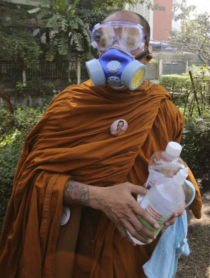 A Thai Buddhist monk holds a bottle of salt water solution, in case of helping anti-government protesters fired by tear gas near the Government House in Bangkok, Monday, Dec. 2, 2013. Thailand's Prime Minister Yingluck Shinawatra on Monday rejected the demands of anti-government protesters locked in street battles with police, saying what they want is unacceptable under the constitution.(AP Photo/Sakchai Lalit)