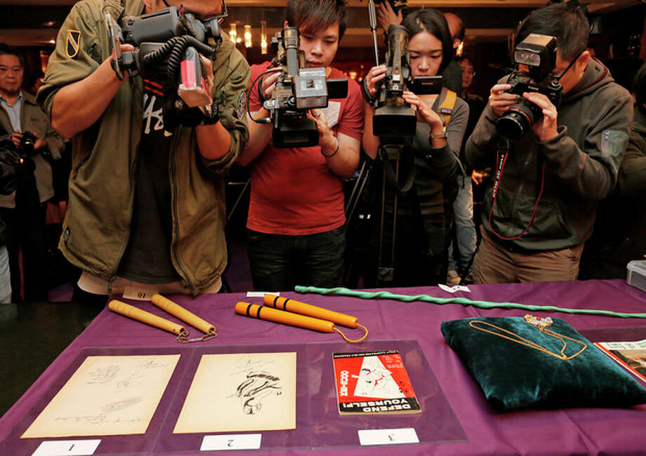 """Bruce Lee's most iconic martial arts weapons, including a pair of yellow lacquered wooden nunchaku, second from left, are displayed during an auction preview in Hong Kong, Monday, Dec. 2, 2013. It's part of a collection of 14 items including clothing and props going on the block on Thursday. Spink auction house estimates props from his movie """"Game of Death"""" to be sold include the nunchaku expected to fetch $26,000-$38,700. (AP Photo/Vincent Yu) / AP"""