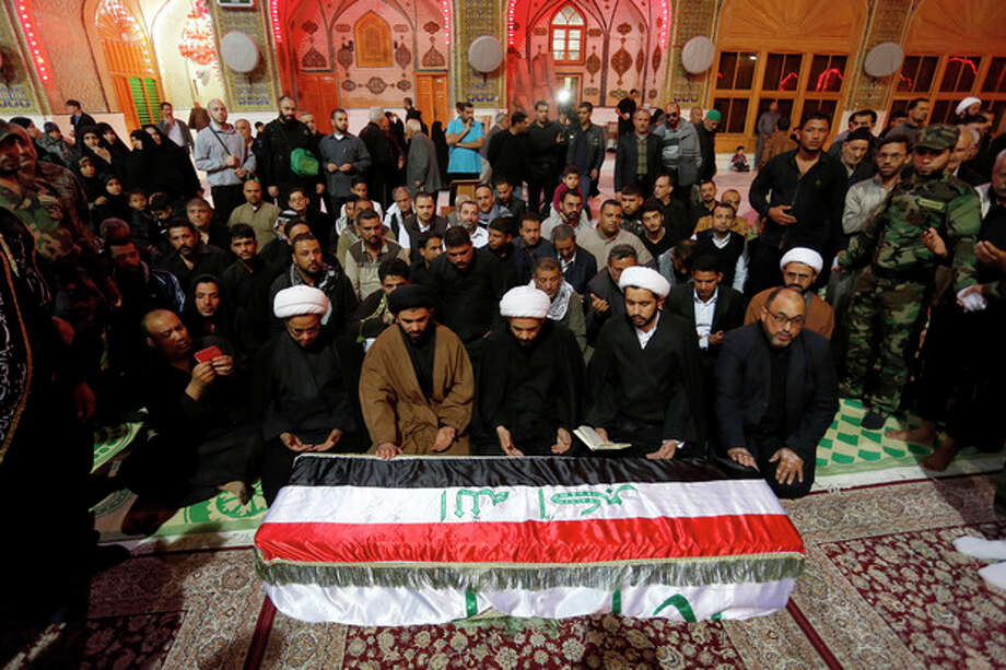 FILE - In this file photo taken Friday, Nov. 29, 2013, mourners pray over the coffin of an Iraqi Shiite fighter, Raed Ali Hussein, during the funeral in the Shiite holy city of Najaf, 100 miles (160 kilometers) south of Baghdad, Iraq. The monthly death toll in Iraq dropped by nearly a third to 659 last month, the U.N. said Sunday, but a recent spike in the number of bullet-riddled bodies found on the street has raised fears the country is facing a return to all-out warfare between Sunni and Shiite factions. (AP Photo, File) / AP