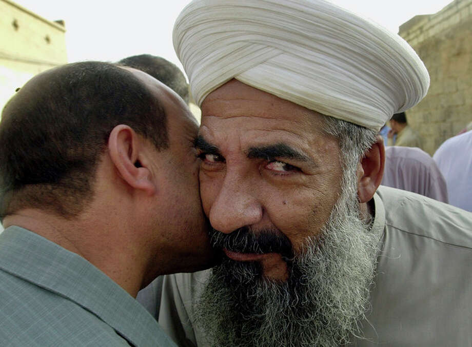 FILE - In this file photo taken Monday, Oct. 18, 2004, Sunni cleric Sheik Khalid al-Jumeili, right, is welcomed by a friend in Fallujah, Iraq, 40 miles (65 kilometers) west of Baghdad, Iraq. Police said gunmen shot dead Sunni cleric Khalid al-Jumeili, an organizer of the western city's Sunni protest camp, in a drive-by shooting. (AP Photo/Bilal Hussein, File) / AP
