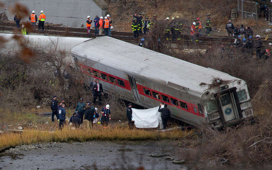 Viewed from Manhattan, first responders and others work at the scene of a derailed Metro North passenger train in the Bronx borough of New York Dec. 1, 2013. The train derailed on a curved section of track in the Bronx early Sunday, coming to rest just inches from the water, killing at least four people and injuring more than 60, authorities said. Police divers searched the waters to make sure no passenger had been thrown in, as other emergency crews scoured the surrounding woods. (AP Photo/Craig Ruttle) / FR61802 AP