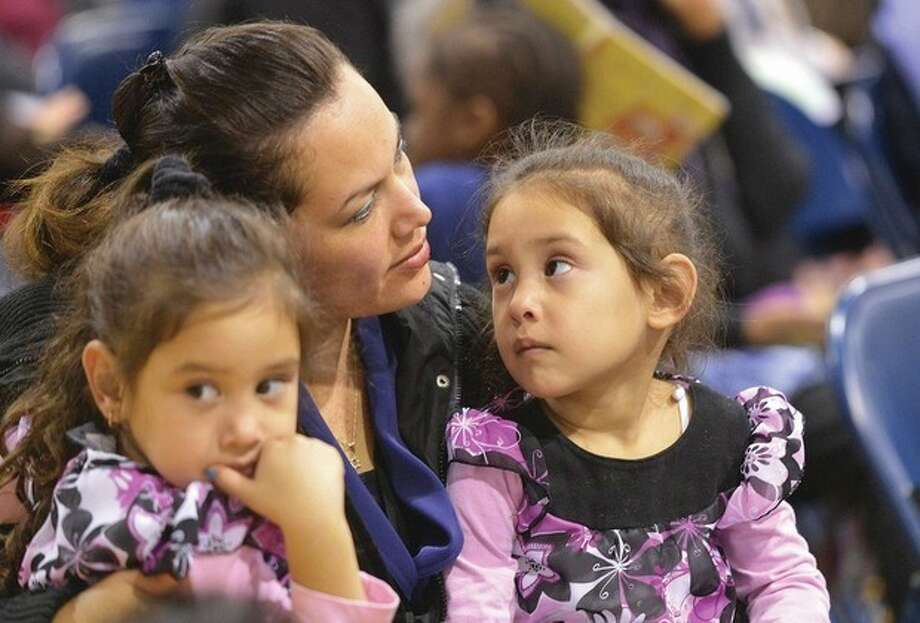 Hour file Photo/Alex von KleydorffGlenda Sierra listens during an October meeting with her twins 4yr old Lindsay and Lillian who are in the Head Start program.