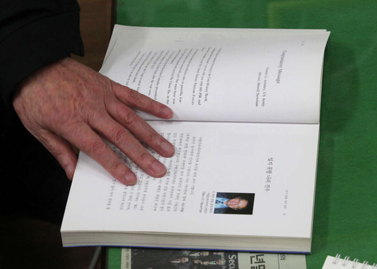 In this Monday, Dec. 2, 2013 photo, a former member of the Kuwol partisan unit, shows a book about the unit that Merrill Newman, an elderly American tourist detained in North Korea signed, praising the South Korean guerrillas and writing that he was ?