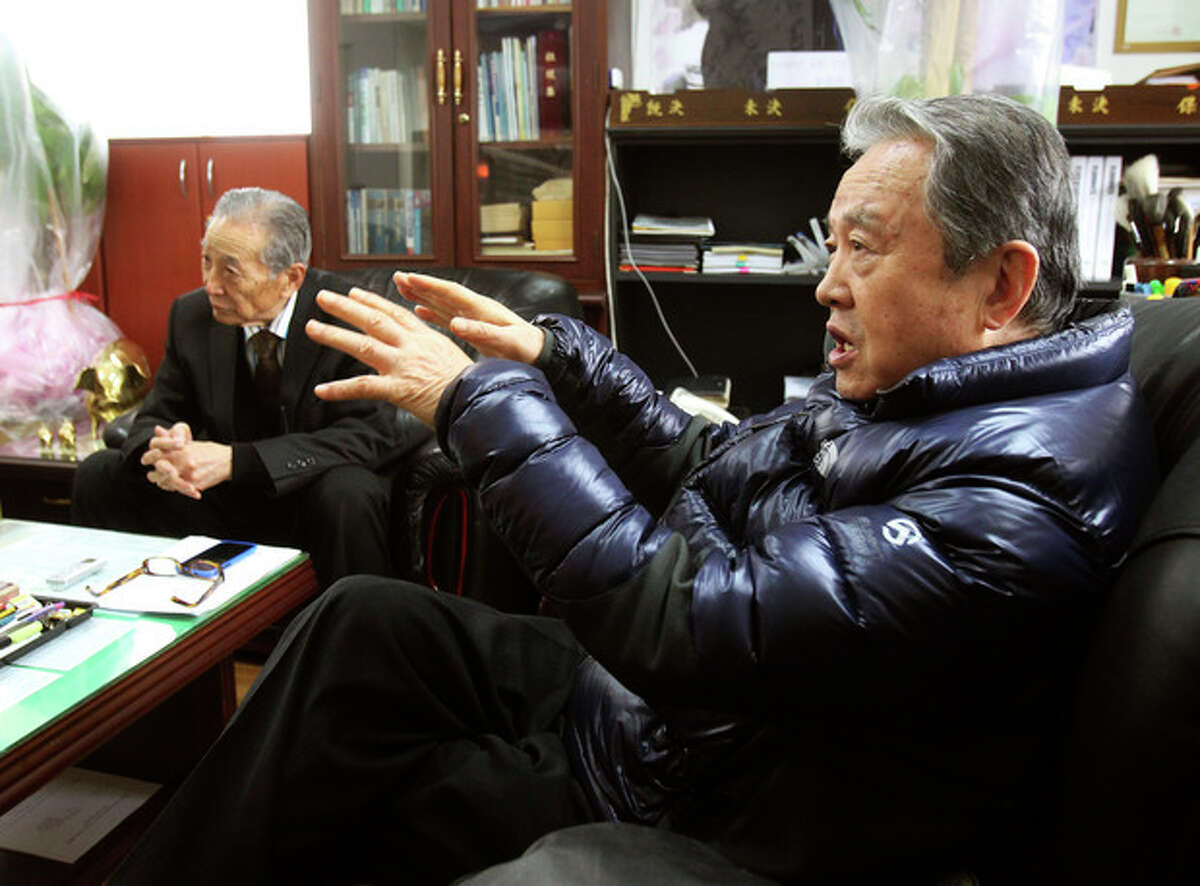 In this Monday, Dec. 2, 2013 photo, Park Young, right, a former member of the Kuwol partisan unit, speaks about Merrill Newman, an elderly American tourist detained in North Korea, during an interview at the Kuwol partisan unit association office in Seoul, South Korea. Six decades before he went to North Korea as a curious tourist, Newman supervised the group of South Korean guerrillas during the Korean War who were perhaps the most hated and feared fighters in the North, former members of the group said. (AP Photo/Ahn Young-joon)