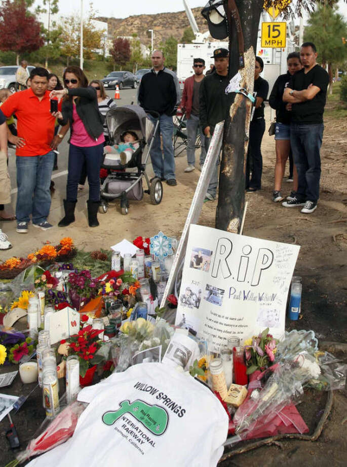 """People view a roadside memorial at the site of the auto crash that took the life of actor Paul Walker and another man, in the small community of Valencia, Calif., Monday, Dec. 2, 2013. The neighborhood where """"Fast & Furious"""" star Walker died in the one-car crash is known to attract street racers, according to law enforcement officials. Walker and his friend and fellow fast-car enthusiast Roger Rodas died Saturday when the 2005 Porsche Carrera GT they were traveling in smashed into a light pole and tree. The two had taken what was expected to be a brief drive away from a charity fundraiser at Rodas' custom car shop in Valencia, about 30 miles (48 kilometers) northwest of Los Angeles. (AP Photo/Nick Ut)"""