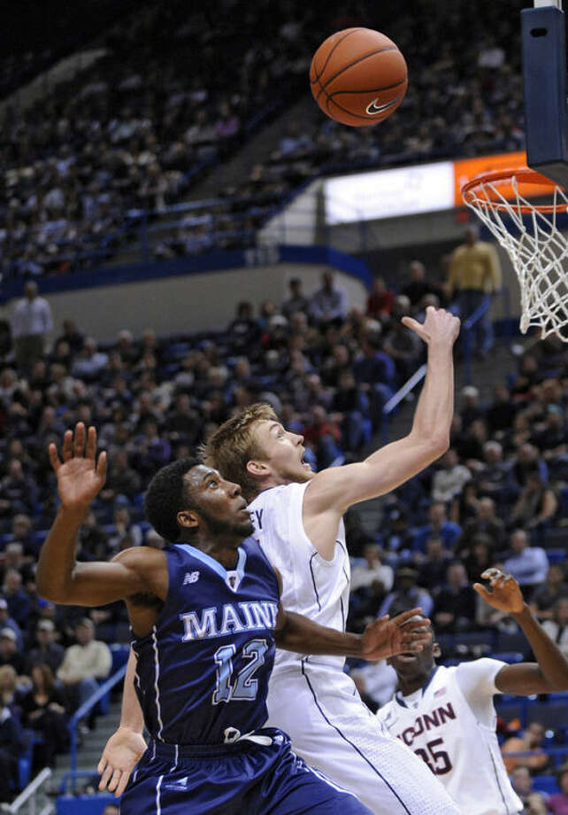 Connecticut's Niels Giffey (5) and Maine's Xavier Pollard (12) fight for a rebound during the first half of an NCAA college basketball game, in Hartford, Conn., on Friday, Dec. 6, 2013. (AP Photo/Fred Beckham)
