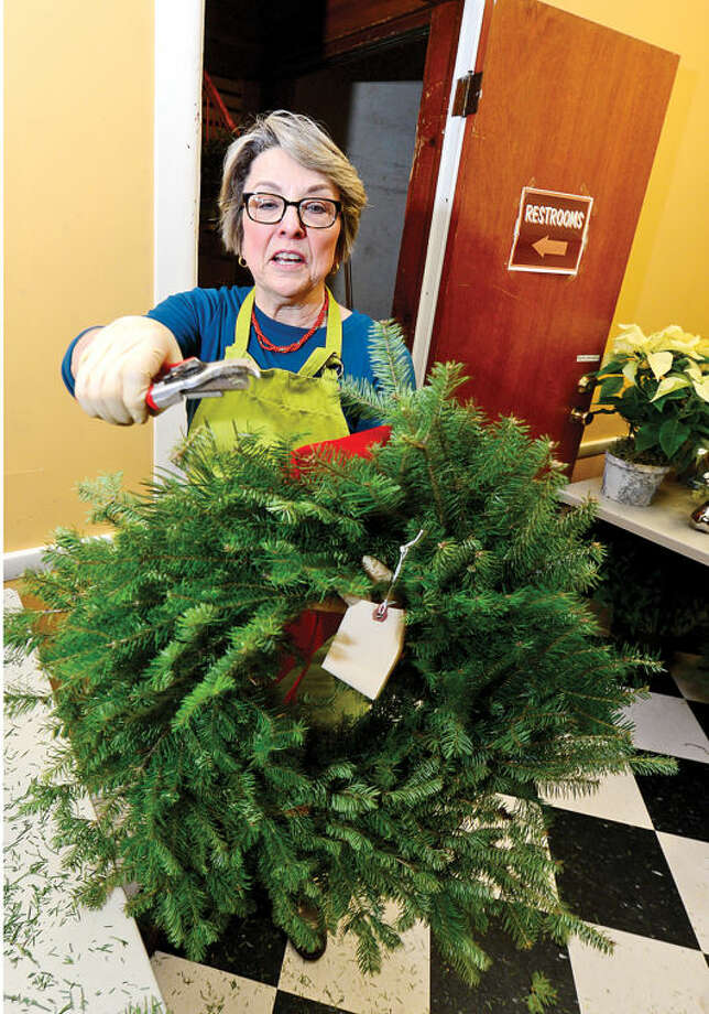 Hour photo / Erik Trautmann Rowayton Gardeners Club members including Nancy Schlater create one-of-a-kind wreaths, boxwoods trees and festive table arrangements for their annual christmas fair this Saturday.