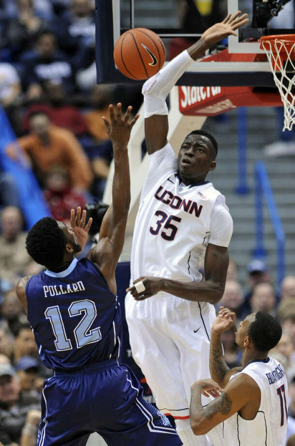 Maine's Xavier Pollard (12) tries to shoot over Connecticut's Amida Brimah (35) during the first half of an NCAA college basketball game, in Hartford, Conn., on Friday, Dec. 6, 2013. (AP Photo/Fred Beckham)