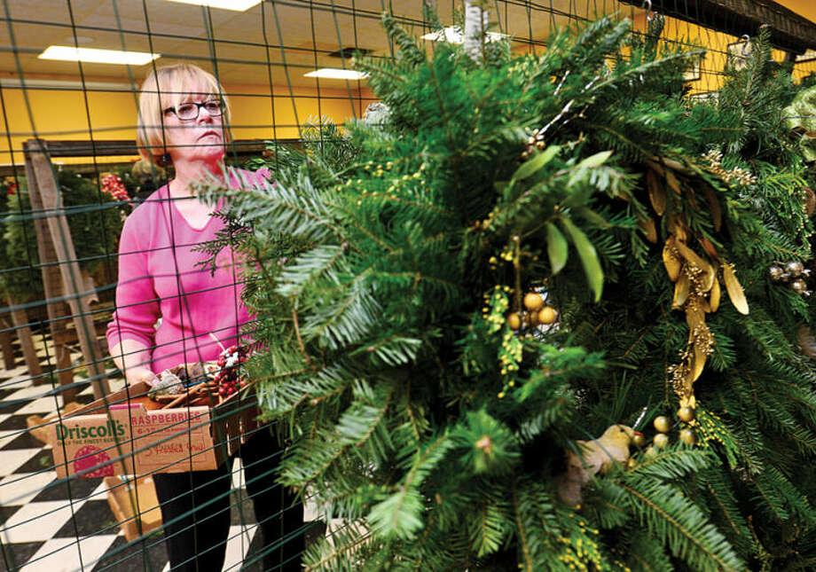 Hour photo / Erik Trautmann Rowayton Gardeners Club members including Mary Verel create one-of-a-kind wreaths, boxwoods trees and festive table arrangements for their annual christmas fair this Saturday.