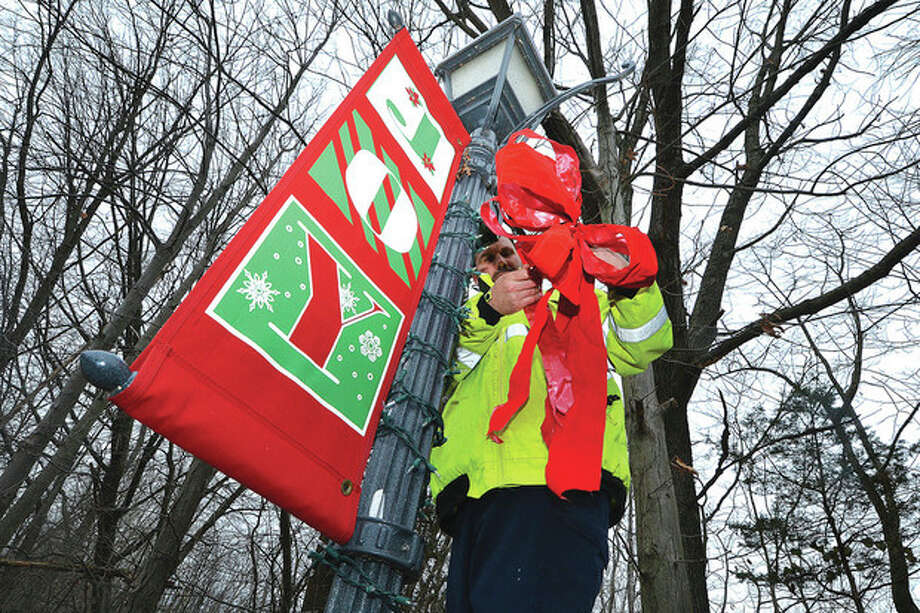 Photo by Alex von KleydorffBruno Mignogna of Wilton Parks & Recreation places a red bow on a lamp post after setting the Joy banner and a string of lights on one of the lampposts in Wilton Center on Monday.