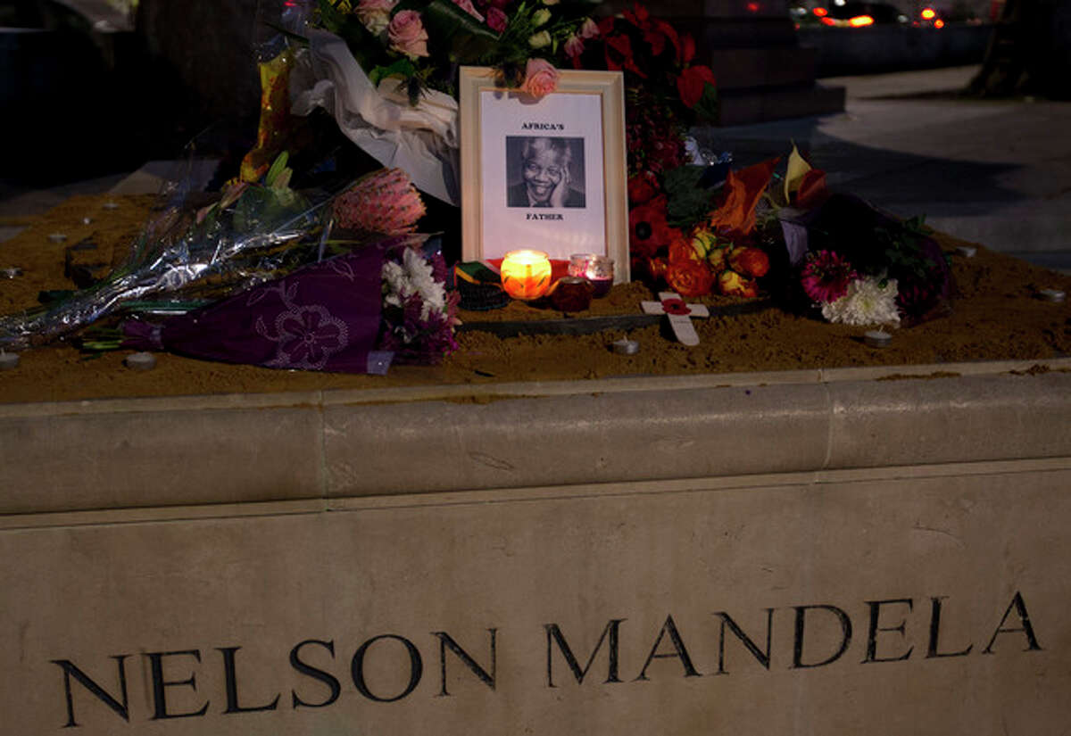 Floral tributes, a framed photograph and candles are laid in memory of former South African president Nelson Mandela beside his statue in Parliament Square, London, Friday, Dec. 6, 2013. Mandela passed away Thursday night after a long illness. He was 95. As word of Mandela's death spread, current and former presidents, athletes and entertainers, and people around the world spoke about the life and legacy of the former South African leader. (AP Photo/Alastair Grant)