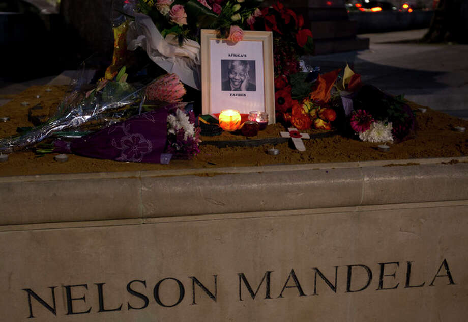 Floral tributes, a framed photograph and candles are laid in memory of former South African president Nelson Mandela beside his statue in Parliament Square, London, Friday, Dec. 6, 2013. Mandela passed away Thursday night after a long illness. He was 95. As word of Mandela's death spread, current and former presidents, athletes and entertainers, and people around the world spoke about the life and legacy of the former South African leader. (AP Photo/Alastair Grant) / AP