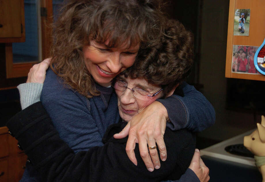 Rhonda Whited-Rupp, left, sister of murder victim Sherry Arnold, gets a hug from friend and co-worker Carmen Latka in the kitchen of Whited-Rupp's home in Sidney, Mont. in this photos made on Nov. 5, 2013. Almost two years after Arnold's murder, the defendant's attorneys are seeking to have him declared unfit for trial due to mental disability. (AP Photo/Matthew Brown) / AP