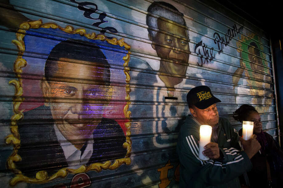"""An artist who goes by the name """"Franco the Great"""" stands in front of a mural of South African leader Nelson Mandela that he painted in 1995, and later added U.S. President Barack Obama, on 125th Street in the Harlem neighborhood of New York, Thursday, Dec. 5, 2013. Mandela, South Africa's first black president, died Thursday after a long illness. He was 95. (AP Photo/John Minchillo) / FR170537 AP"""
