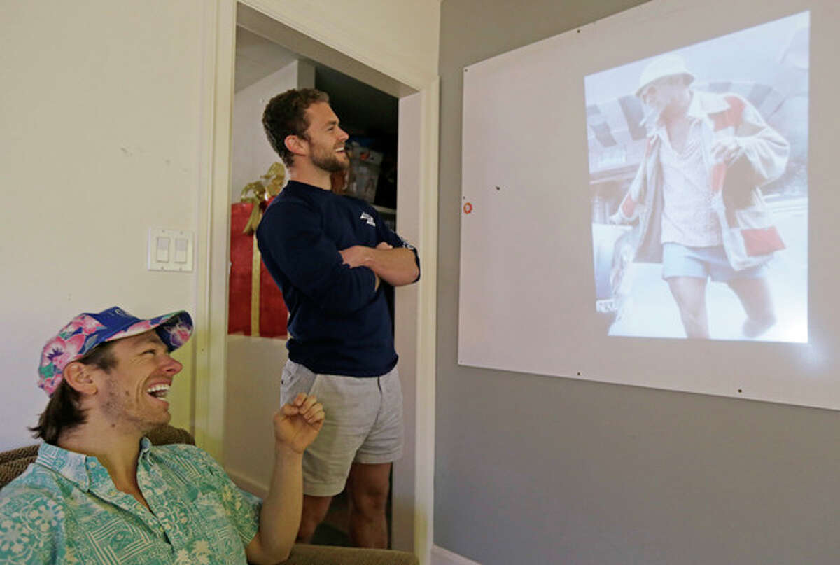 In this photo taken Wednesday, Dec. 4, 2013, co-founders Preston Rutherford, left, and Tom Montgomery, right, review user generated content for the upcoming week's social posts at the headquarters of Chubbies Shorts in San Francisco. Chubbies uses Facebook for marketing tools like videos that users will share with their friends. It uses Twitter for conversations with customers, and posts photos on Instagram to create buzz about their products. (AP Photo/Eric Risberg)