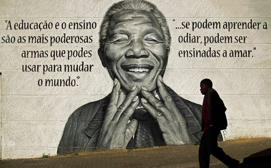 """A man walks past a mural of the former South African President Nelson Mandela that reads in Portuguese: """"Eduction and teaching are the most powerful weapons which you can use to change the world"""", left, and """"if people can learn to hate, they can be taught to love"""", in Loures, on the outskirts of Lisbon, Portugal, Friday, Dec. 6, 2013. Mandela passed away Thursday night after a long illness. He was 95. As word of Mandela's death spread, current and former presidents, athletes and entertainers, and people around the world spoke about the life and legacy of the former South African leader. (AP Photo/Francisco Seco) / AP"""