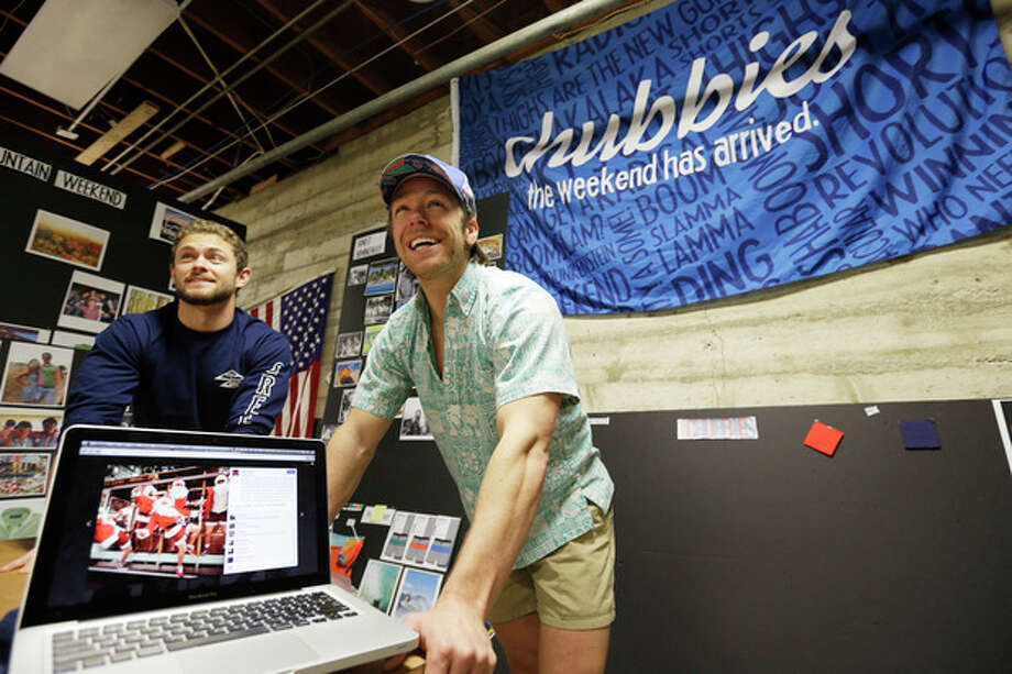 In this photo taken Wednesday, Dec. 4, 2013, co-founders Tom Montgomery, left, and Preston Rutherford, right, stand behind a laptop showing an Instagram from a holiday photo shoot at the headquarters of Chubbies Shorts in San Francisco. Chubbies uses Facebook for marketing tools like videos that users will share with their friends. It uses Twitter for conversations with customers, and posts photos on Instagram to create buzz about their products. (AP Photo/Eric Risberg) / AP