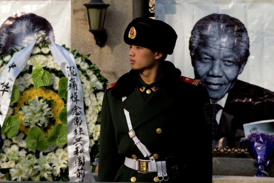 A Chinese paramilitary policeman stands guard near a wreath of flowers and a portrait of former South African President Nelson Mandela displayed outside the South African Embassy in Beijing, Friday, Dec. 6, 2013. South Africa's President Jacob Zuma said Mandela has died at age 95. (AP Photo/Andy Wong) / AP