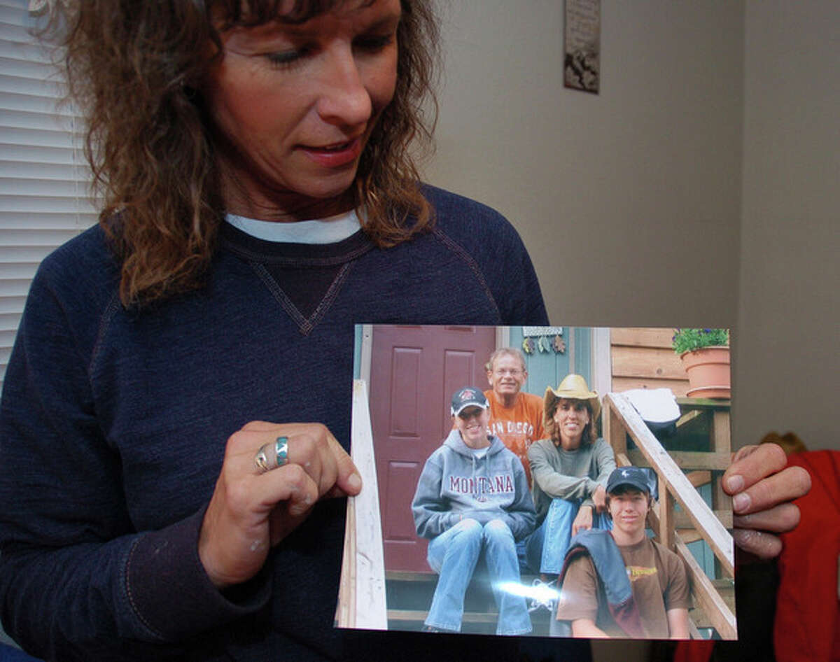 Rhonda Whited-Rupp holds a picture of sister Sherry Arnold, seen in a cowboy hat, and Arnold?'s family in this Nov. 5, 2013 photo made in Sidney, Mont. As attorneys for one of the men arrested in Arnold?'s murder seek to have him declared unfit for trial. (AP Photo/Matthew Brown)