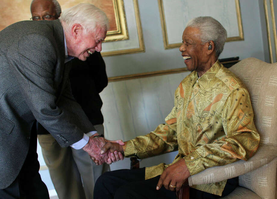 FILE - In this Saturday, May 29, 2010, file photo, former South African President Nelson Mandela, right, shakes hands with former U.S. President Jimmy Carter, during a reunion with The Elders, three years after he launched the group, in Johannesburg, South Africa. Mandela died Thursday, Dec. 5, 2013, after a long illness. He was 95. (AP Photo/Jeff Moore, Pool, File) / Pool Jeff Moore