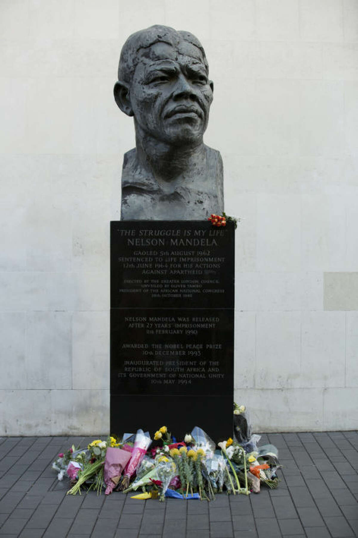 Flowers are seen underneath a statue of former South African president Nelson Mandela, at the side of the Royal Festival Hall on the south bank of London, Friday, Dec. 6, 2013. Mandela passed away Thursday night after a long illness. He was 95. As word of Mandela's death spread, current and former presidents, athletes and entertainers, and people around the world spoke about the life and legacy of the former South African leader. (AP Photo/Jon Super)