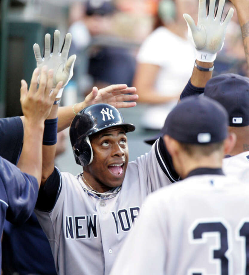 FILE - In this Aug. 6, 2012 file photo, New York Yankees' Curtis Granderson celebrates in the dugout after scoring on a double by Robinson Cano in the fifth inning of a baseball game against the Detroit Tigers, in Detroit. A person familiar with the situation says free-agent outfielder Granderson and the New York Mets have agreed to a $60 million, four-year contract. The person spoke to The Associated Press on condition of anonymity Friday, Dec. 6, 2013, because the deal was pending a physical and no announcement had been made. (AP Photo/Duane Burleson, File) / FR38952 AP