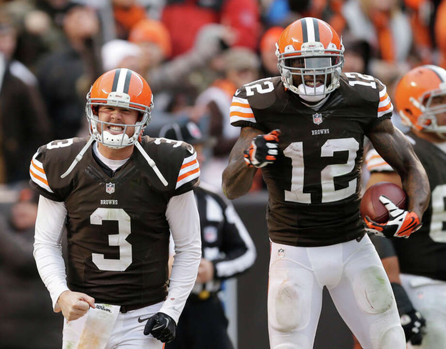 Cleveland Browns quarterback Brandon Weeden (3) celebrates with wide receiver Josh Gordon (12) after they connected on a 95-yard touchdown pass in the fourth quarter of an NFL football game against the Jacksonville Jaguars, Sunday, Dec. 1, 2013, in Cleveland. (AP Photo/Tony Dejak) / AP