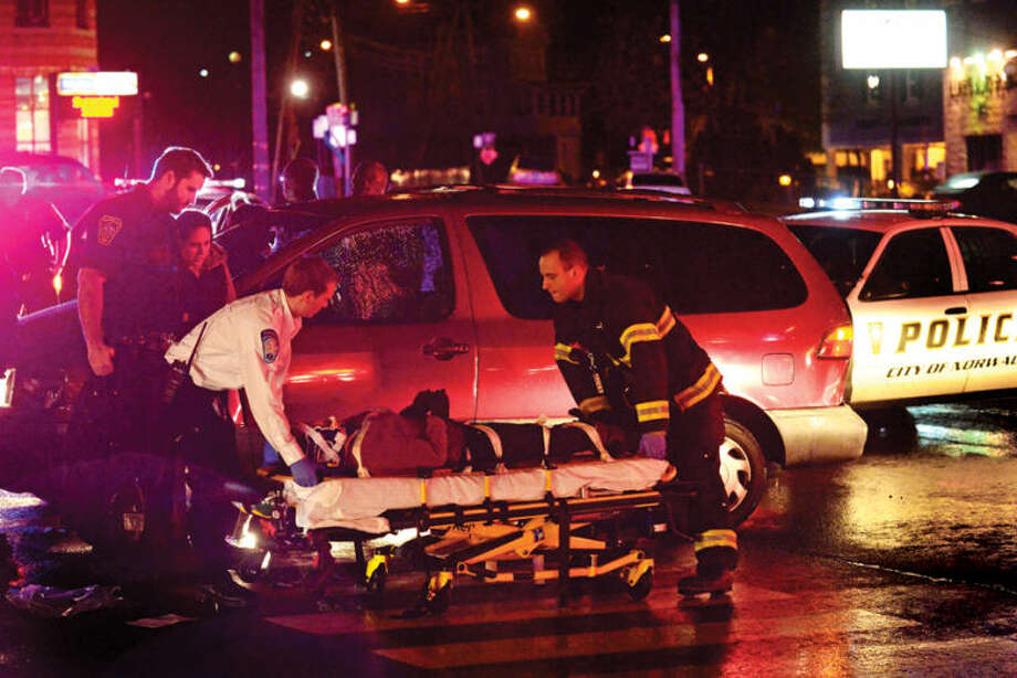 Hour photo / Erik Trautmann A woman is loaded onto a gurney after being hit by a motor vehicle at the intersection of West Cedar St and Connecticut Ave Friday night. Hour photo / Erik Trautmann