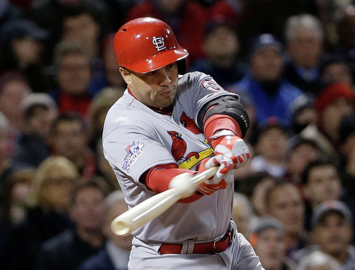 FILE - In this Oct. 24, 2013, file photo, St. Louis Cardinals' Carlos Beltran hits an RBI single during Game 2 of baseball's World Series against the Boston Red Sox in Boston. Two people familiar with the negotiations say outfielder Carlos Beltran and the New York Yankees have agreed to a $45 million, three-year contract. (AP Photo/David J. Phillip, File)