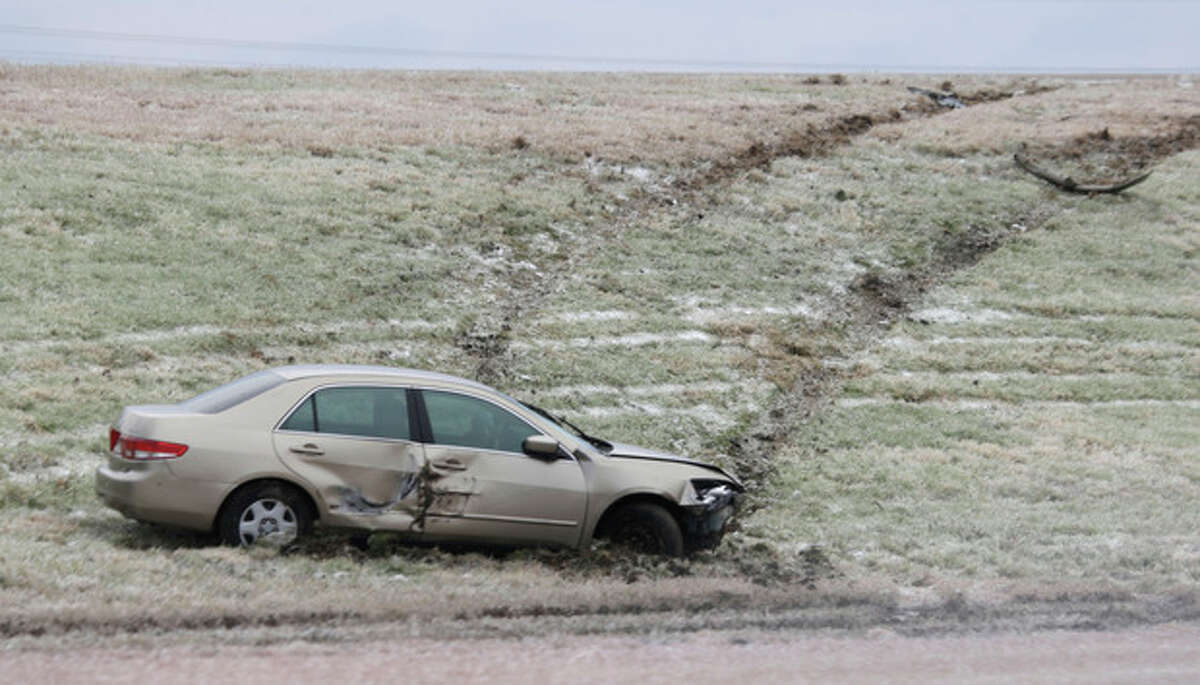 A car that slid off the road sits on the side of the highway near Waxahachie, Texas on Saturday, Dec. 7, 2013. Icy conditions are expected to last through the weekend from Texas to Ohio to Tennessee from a cold snap that covered much of the nation. (AP Photo/LM Otero)