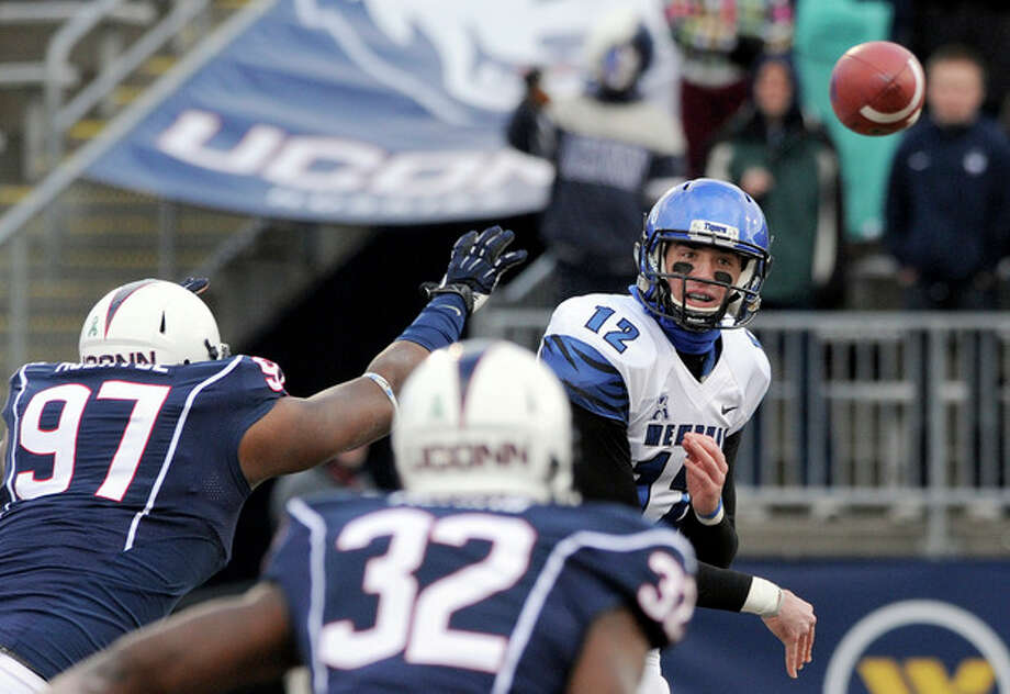 Memphis quarterback Paxton Lynch (12) passes while pressured by Connecticut defensive end B.J. McBryde (97) and Connecticut linebacker Jefferson Ashiru (32) during the first half of an NCAA college football game in East Hartford, Conn., on Saturday, Dec. 7, 2013. (AP Photo/Fred Beckham) / FR153656 AP