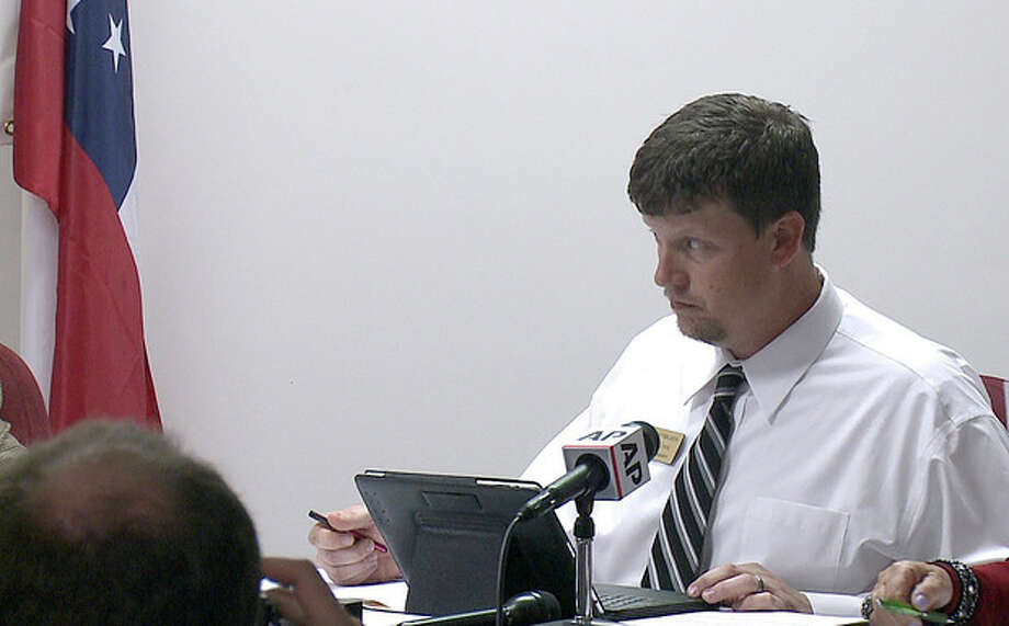 """FILE - In this Monday, April 1, 2013 file image made from video, Nelson City Council Member Duane Cronic seconds the motion for a vote of the """"Family Protection Ordinance"""" which required mandatory gun ownership for all heads-of-household in Nelson, Ga. Earlier in the year, a local tea party activist suggested to Cronic that the town should have a law requiring everyone to own a gun. After the Brady Center to Prevent Gun Violence sued the town in support of Lamar Kellett, the law's most vocal critic, the council agreed in late August to revise the measure to make clear that gun ownership is a choice and that a requirement could not be enforced. (AP Photo/Johnny Clark) / AP"""