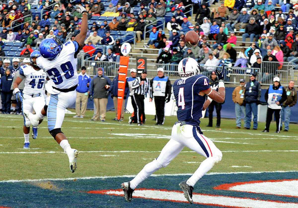 Connecticut wide receiver Deshon Foxx (4) gets by Memphis defensive back Reggis Ball (39) for a touchdown during the first half of an NCAA college football game, in East Hartford, Conn., on Saturday, Dec. 7, 2013. (AP Photo/Fred Beckham)